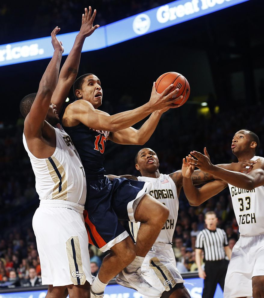 Virginia's Malcolm Brogdon (15) puts up a shot against Georgia Tech's Charles Mitchell, from left, Marcus Georges-Hunt, and James White in the first half of an NCAA college basketball game Saturday, Jan. 9, 2016, in Atlanta. (AP Photo/David Goldman)