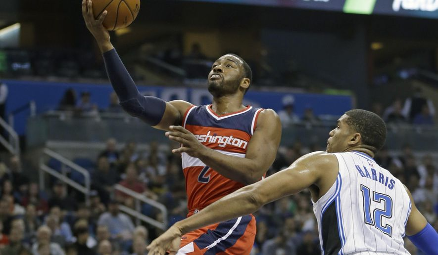 Washington Wizards' John Wall (2) goes past Orlando Magic's Tobias Harris (12) to score a basket during the first half of an NBA basketball game, Saturday, Jan. 9, 2016, in Orlando, Fla. (AP Photo/John Raoux)