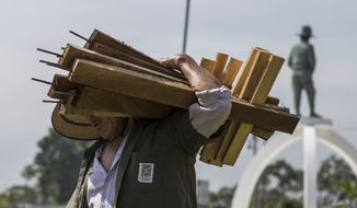 A city employee removes wooden crosses that were placed in a plaza by organizations protesting against government inaction over the alarming murder rate in San Salvador, El Salvador, on Sept. 1, 2015. (Associated Press)
