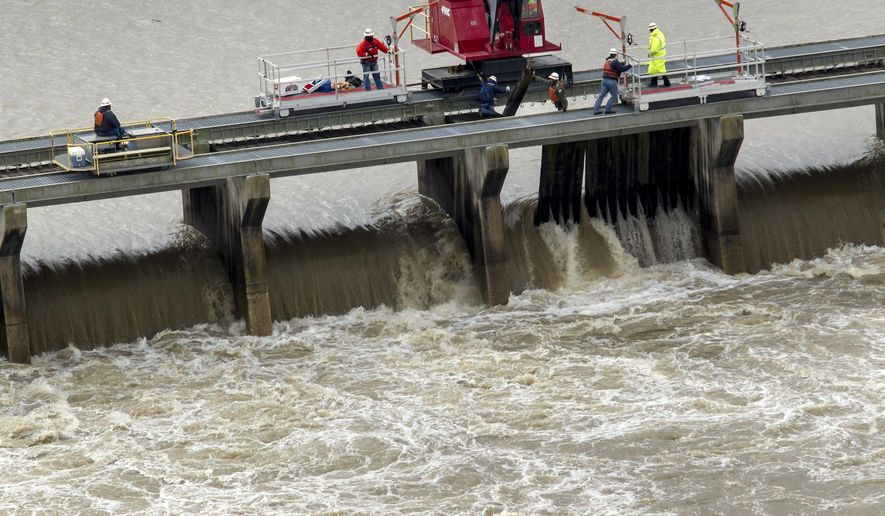 CORRECTS TO REFLECT POOL STATUS OF PHOTO - Workers with the U.S. Army Corps of engineers pull wooden pins to drain water from the Mississippi River into the Bonnet Carre Spillway Sunday, Jan. 10, 2016, in Norco, La. The Mississippi River water levels are rising because of heavy December rain in the Midwest. The opening of the Bonnet Carre Spillway helps relieve pressure on New Orleans-area levees by making sure the water doesn't flow faster than 1.25 million cubic feet per second through the city.  (Scott Threlkeld/The Advocate via AP, Pool)