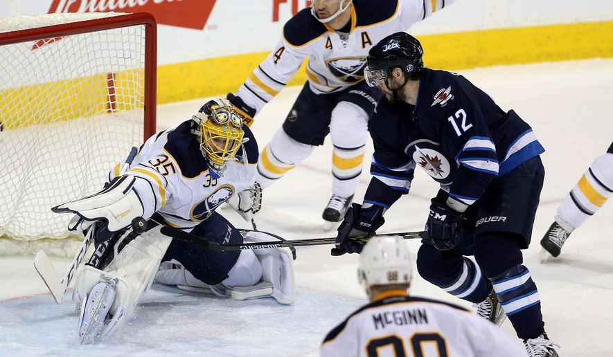 Buffalo Sabres' goaltender Linus Ullmark (35) makes a difficult save on Winnipeg Jets' Drew Stafford (12) during first-period NHL hockey game action in Winnipeg, Manitoba, Sunday, Jan. 10, 2016. (Trevor Hagan/The Canadian Press via AP) MANDATORY CREDIT
