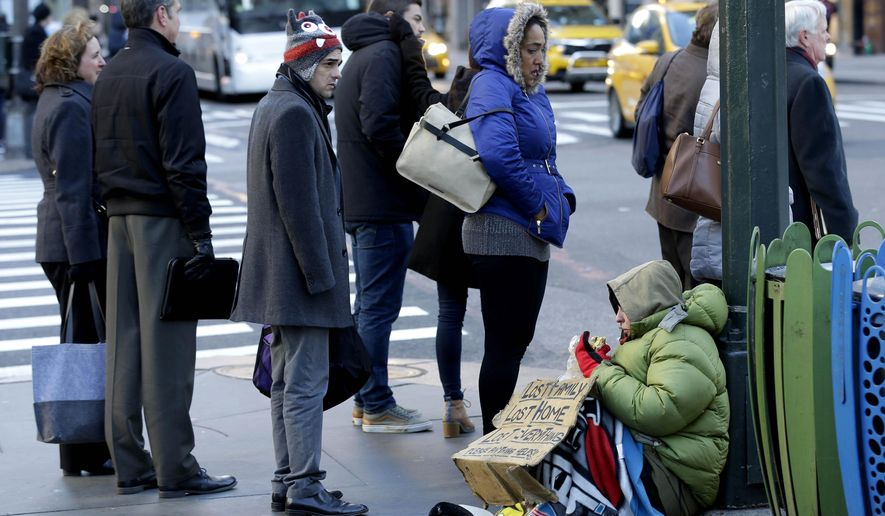 FILE - In this Jan. 5, 2016, file photo, a homeless woman, who only wanted to be identified as Lala, asks for money on a street corner in midtown Manhattan in New York. As bitter winter weather arrived in the Northeast, New York Gov. Andrew Cuomo issued an executive order requiring the homeless to be forcibly removed from the streets in freezing temperatures. The Associated Press spoke to about three dozen people living on the city's streets about how, or even if, new policies on the homeless announced by Cuomo and New York Mayor Bill de Blasio are affecting them. (AP Photo/Seth Wenig, File)