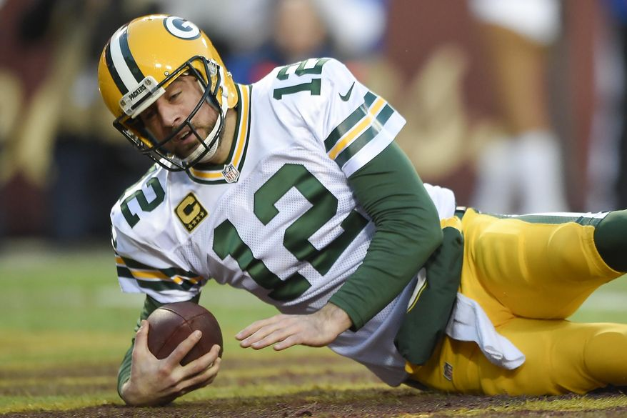 Green Bay Packers quarterback Aaron Rodgers (12) bounces off the turf in the end zone after being sacked for a safety during the first half of an NFL wild card playoff football game against the Washington Redskins in Landover, Md., Sunday, Jan. 10, 2016. (AP Photo/Nick Wass)