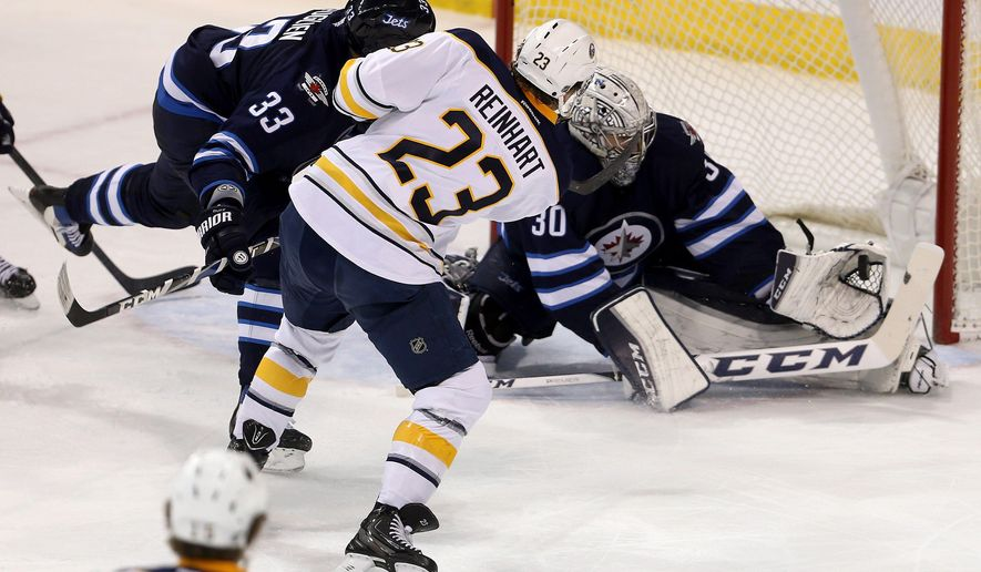 Winnipeg Jets' goaltender Connor Hellebuyck (30) makes a glove save on Buffalo Sabres' Sam Reinhart (23) with Dustin Byfuglien (33) defending during first-period NHL hockey game action in Winnipeg, Manitoba, Sunday, Jan. 10, 2016. (Trevor Hagan/The Canadian Press via AP) MANDATORY CREDIT