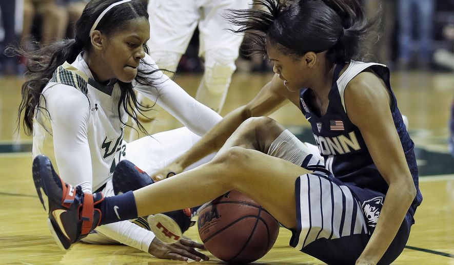 South Florida guard Courtney Williams, left, and Connecticut's Moriah Jefferson battle for a loose ball during the first half of an NCAA college basketball game Sunday, Jan. 10, 2016, in Tampa, Fla. (AP Photo/Chris O'Meara)