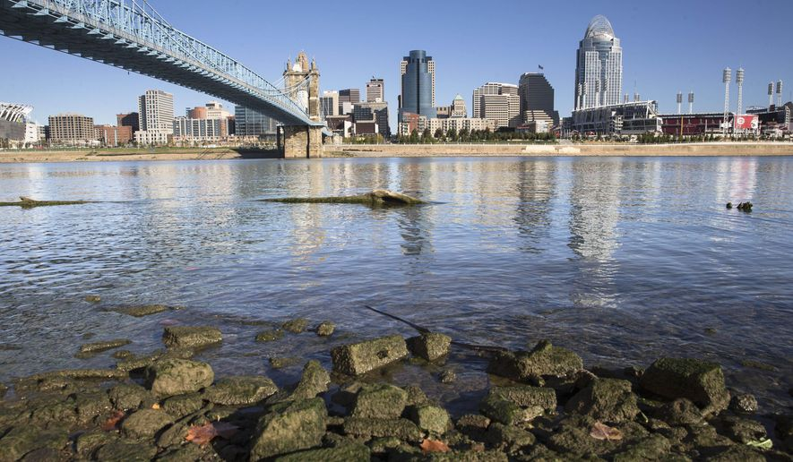 FILE - This file photo taken Oct. 16, 2015, shows algae coating rocks on the banks of the Ohio River in Newport, Ky., overlooking the Cincinnati skyline. In December 2015, Ohio state officials rejected a request by two wastewater plants operated by Dayton, Ohio, and Montgomery County, Ohio, seeking to delay the Ohio Environmental Protection Agency's order to reduce phosphorus released into the Great Miami River, a tributary of the Ohio River, in an effort to curtail algae blooms. (AP Photo/John Minchillo, File)