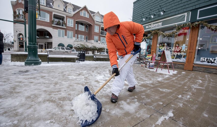Robert Lovelace, an employee of Sun and Snow Sports shop, shovels the ice and snow from in front of the store in downtown Plymouth, Mich., on Sunday, Jan. 10, 2016. The National Weather Service is warning of hazardous road conditions across parts of southeast Michigan due to falling snow and dropping temperatures.  (David Guralnick/The Detroit News)