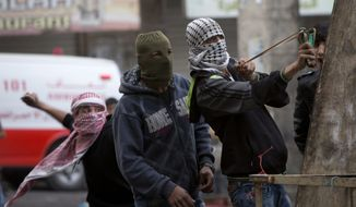 A Palestinian protester uses a slingshot during clashes with Israeli soldiers after a funeral in Hebron, home to about 850 Jewish settlers in a population of 170,000. (Associated Press)