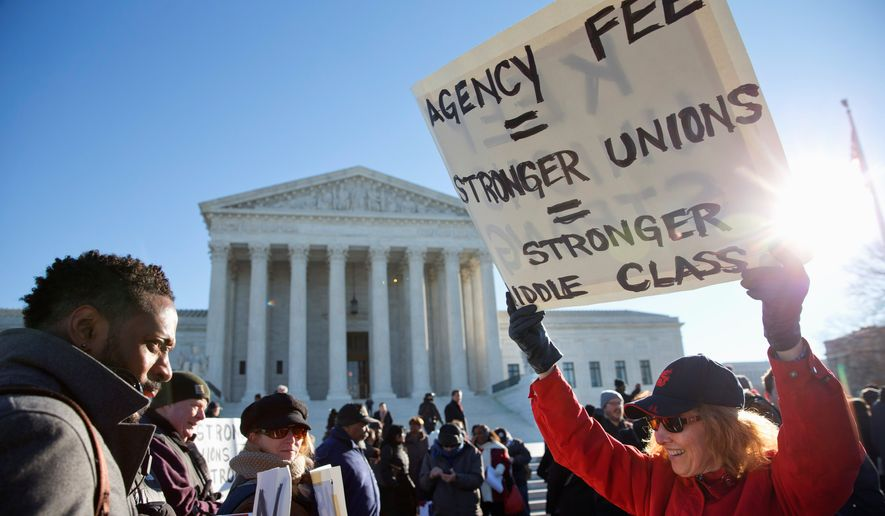 Union supporters rally at the Supreme Court Monday as the court heard arguments in Friedrichs v. California Teachers Association, a case that challenges the right of public employee unions to collect fees from workers who opt out of membership. (Associated Press)