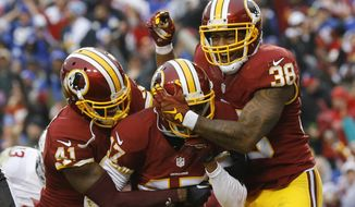 Washington Redskins cornerback Quinton Dunbar, center, is mobbed by his teammates cornerback Will Blackmon (41) and free safety Dashon Goldson (38) after he intercepted a pass in the end zone intended for New York Giants wide receiver Rueben Randle during the second half of an NFL football game in Landover, Md., Sunday, Nov. 29, 2015. (AP Photo/Patrick Semansky)
