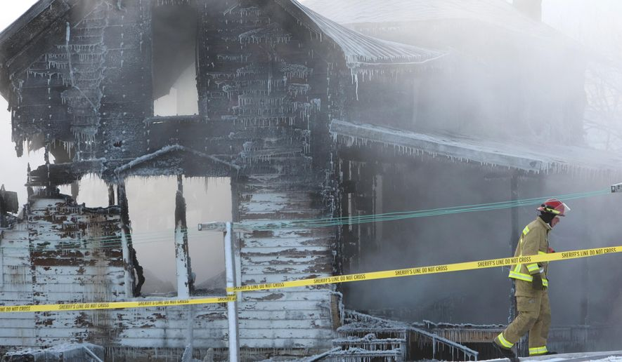 A firefighter from Harmony, Minn., walks past the smoldering remains of a fire at an Amish home north of Canton, Minn., Monday morning Jan.11, 2016. Authorities say two people are missing and two others have been injured in the fire. (Ken Klotzbach/The Rochester Post-Bulletin via AP) MANDATORY CREDIT