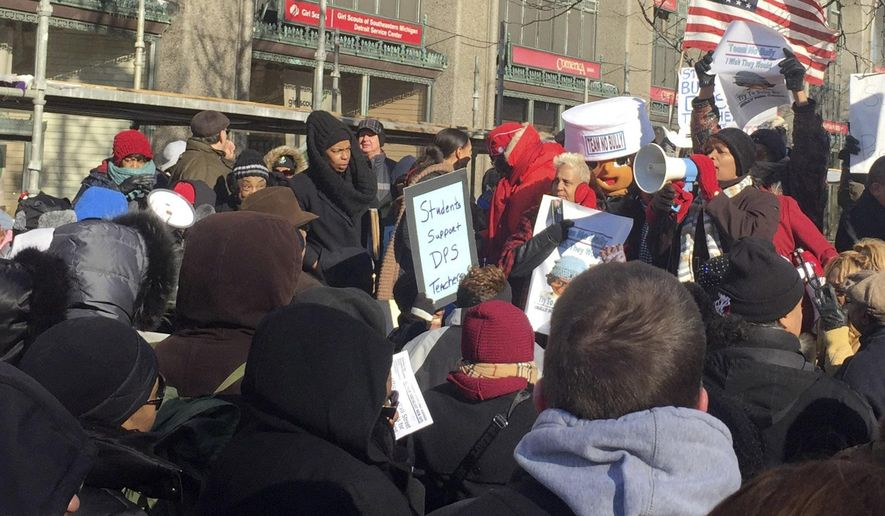 A group of over a hundred teachers, joined by parents and children, protest on Monday, Jan. 11, 2016, in Detroit. (Kim Kozlowski/Detroit News via AP)