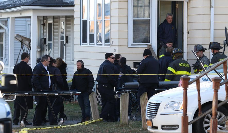 Emergency personnel gather Monday, Jan. 11, 2016 at a house where four people were found dead late Sunday after a fire in Rochester, NY. Officials say firefighters found the bodies of four people, two men and two women, while battling the blaze. The fire has been deemed suspicious, but officials haven't released any details of what may have caused the fire or what killed the four victims. (Tina Macintyre-Yee/Democrat & Chronicle via AP)  MAGS OUT; NO SALES; MANDATORY CREDIT