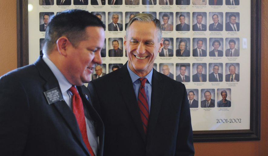 FILE - In this Dec. 8, 2015 file photo, South Dakota Gov. Dennis Daugaard speaks with Senate Majority Leader Corey Brown shortly before the governor outlined his proposed budget for the 2016 legislative session at the state Capitol in Pierre, S.D. Daugaard will give his state of the state address Tuesday, Jan. 12 to kick off the 2016 legislative session. (AP Photo/James Nord, File)