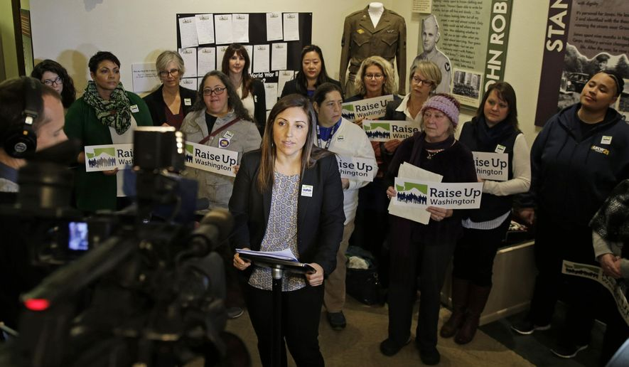 Teresa Mosqueda, center, campaign director for the Washington State Labor Council, stands with supporters, Monday, Jan. 11, 2016, in Olympia, Wash., as she talks about the filing of a ballot measure with in the Secretary of State's office to incrementally raise Washington's minimum wage to $13.50 an hour over four years starting in 2017, and provide paid sick leave to employees without it. (AP Photo/Ted S. Warren)