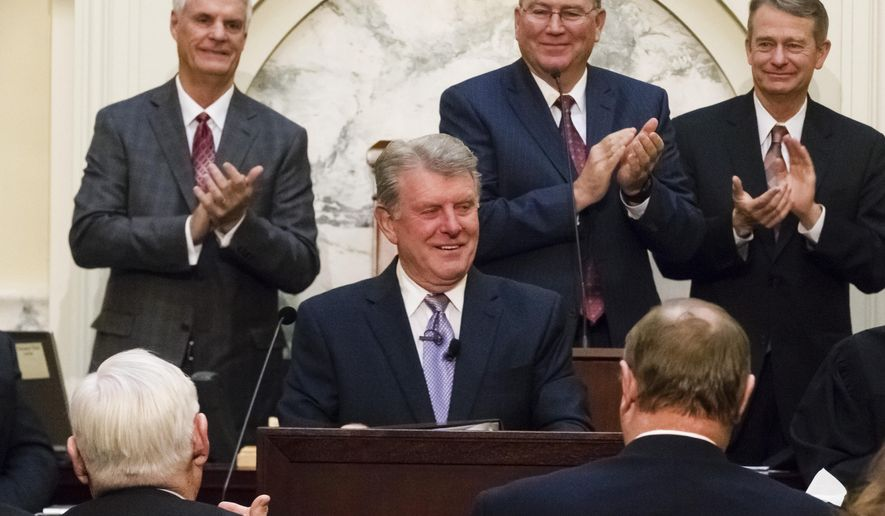 """Idaho Gov. C.L. """"Butch"""" Otter, center, smiles at the conclusion of his State of the State address inside the House chambers at the state Capitol building on Monday, Jan. 11, 2016, in Boise, Idaho. Behind Otter, from left to right, are: President Pro Tem Sen. Brent Hill, R-Rexburg; Speaker of the House Rep. Scott Bedke, R-Oakley; and Lt. Gov. Brad Little. (AP Photo/Otto Kitsinger)"""