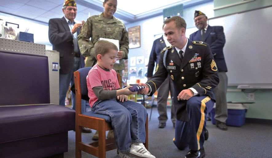 In a Friday, Dec. 11, 2015, file photo, Logan Barritt, 4, receives a small American flag from Army recruiter Staff Sgt. .Jordan Whitlow in Janesville, Wis., during a thank you ceremony for Logan's efforts in raising more than $1,200 for holiday care packages to soldiers stationed overseas at the Young Women's Christian Association. Logan will be one of House Speaker Paul Ryan's guests for President Barack Obama's final State of the Union address. (Anthony Wahl/The Janesville Gazette via AP)