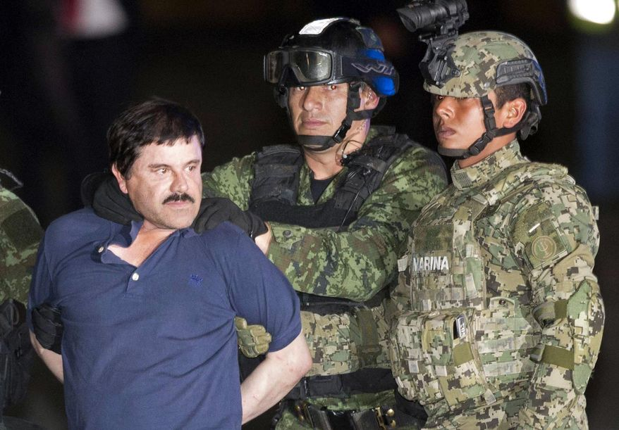 """In this Friday, Jan. 8, 2016 photo, Joaquin """"El Chapo"""" Guzman is made to face the press as he's escorted to a helicopter in handcuffs by soldiers and marines at a federal hangar in Mexico City. Guzman's second prison escape in 2015 from a top security prison though a tunnel had embarrassed President Enrique Pena Nieto and made his capture a national priority. (AP Photo/Eduardo Verdugo)"""