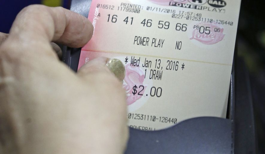 A grocery store clerk pulls a Powerball lottery ticket from the printer in Hialeah, Fla., Monday, Jan. 11, 2016. The Powerball jackpot has grown to over 1 billion dollars. (AP Photo/Alan Diaz)