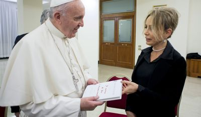 Pope Francis receives the Italian edition of his book ' The name of God is mercy ', by Marina Berlusconi, president of Mondadori, at the Vatican Monday, Jan. 11, 2016. A delegation of Mondadori publishing company gave a copy of the first book of the Pope Francis' papacy to the pontiff, on Monday afternoon. ' The Name of God Is Mercy ' is a 100-page conversation with Italian journalist Andrea Tornielli. (L'Osservatore Romano/Pool Photo via AP)