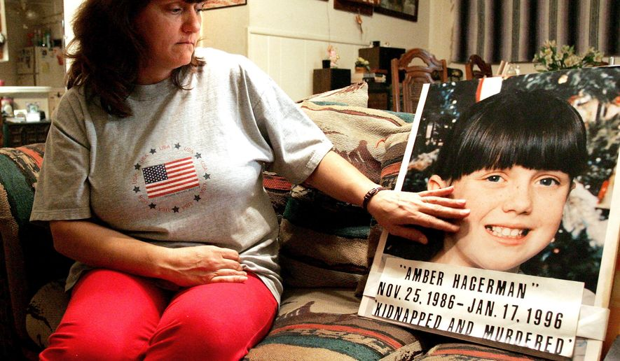 FILE - In this Jan. 12, 2006 file photo, Donna Norris touches a photo of her daughter, Amber Hagerman, at her Hurst, Texas, home. The 1996 slaying of the North Texas girl that led to the Amber Alert notification system to find missing children remains unsolved. Arlington police on Tuesday, Jan. 12, 2016, repeated their request for tips in finding the killer of the 9-year-old. Amber's mother, now named Donna Williams, appealed for justice for her daughter. (R. Jeena Jacob/Star-Telegram via AP)  MAGS OUT; INTERNET OUT; MANDATORY CREDIT