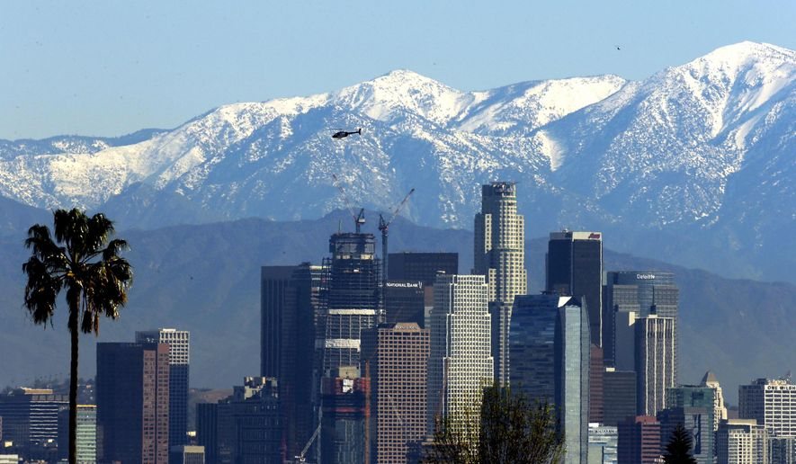 The snow-capped San Gabriel Mountains stand as a backdrop to the downtown Los Angeles skyline, Tuesday, Jan. 12, 2016. Southern California has warmed under sunny skies after a weak offshore flow pushed out clouds, but the scenic vistas of snow-capped mountains from last week's storms will be short-lived. The National Weather Service says a front will push through the area Wednesday, bringing rain to the Central Coast but little more than cloud cover to the south.(AP Photo/Nick Ut)