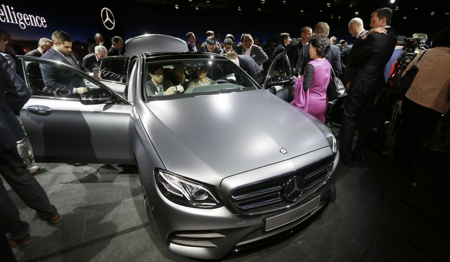 FILE - In this Sunday, Jan. 10, 2016, file photo, journalists look over the Mercedes-Benz new E-Class sedan during a preview night for the North American International Auto Show, in Detroit. The Mercedes-Benz E-Class can change lanes by itself and maintain a safe distance from the car in front of it at speeds up to 130 miles per hour. (AP Photo/Carlos Osorio, File)