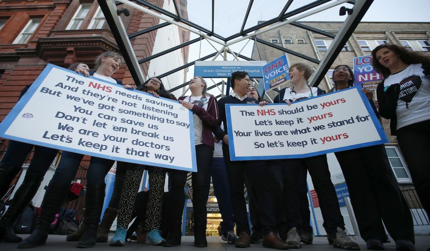 The British National Heath Service Singers, who are either doctors or nurses, perform a protest song in support of junior doctors outside Great Ormond Street Hospital for Sick Children, as a 24 hour junior doctor strike starts in London, Tuesday, Jan. 12, 2016. Thousands of junior doctors have walked off the job in England in a dispute over pay and working conditions - the first such strike in 40 years. Some 50,000 junior doctors - who represent a third of the medical workforce - are on strike for 24 hours amid government plans to change pay and work schedules. (AP Photo/Alastair Grant)