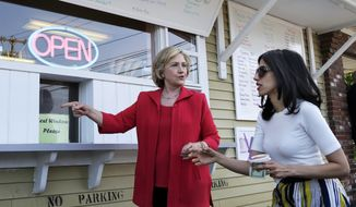 FILE - In this July 3, 2015, file photo, Democratic presidential candidate Hillary Clinton, left, and her personal aide Huma Abedin approach a window to buy ice cream at Dairy Twirl in Lebanon, N.H. The State Department has agreed to review 29,000 pages of emails from Abedin from their days at the State Department for possible public release under a new legal agreement with a conservative legal group. But many of the emails from Abedin would not be publicly released until six months after the election. (AP Photo/Elise Amendola, file)