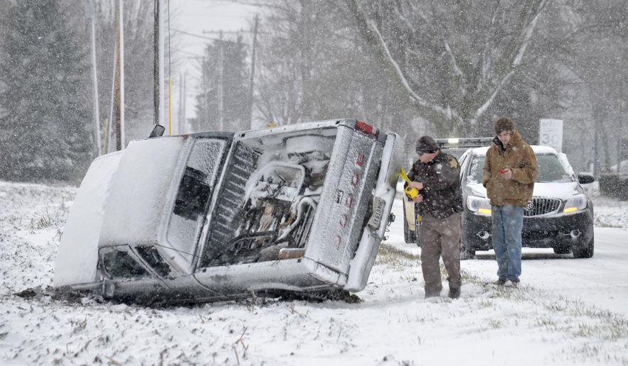A Grant County Sheriff's Deputy checks the scene of a non-injury rollover accident just north of Sims, Ind., Monday, Jan. 11, 2016. Subfreezing temperatures and blowing snow made roads slick and hazardous. (Jeff Morehead/The Chronicle-Tribune via AP) MANDATORY CREDIT