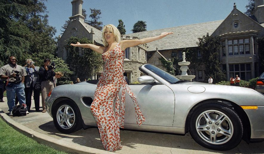 CORRECTS SPELLING OF LAST NAME TO HEFNER FROM HEFFNER - File - In this May 1, 1997, file photo, Victoria Silvstedt poses with her brand new Porsche in front of the Playboy Mansion in Beverly Hills, Calif. The Playboy Mansion is up for sale but longtime resident Hugh Hefner wants to stay put. Playboy Enterprise announced the West Los Angeles estate, the backdrop of many film shoots and wild parties, was listed on Monday, Jan. 11, 2016, for $200 million. (AP Photo/Chris Pizzello, File)
