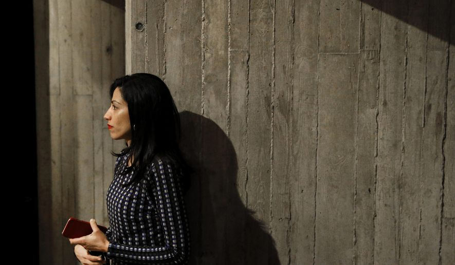 Huma Abedin, longtime aide to Democratic presidential candidate Hillary Clinton, watches as Clinton greets attendees after a campaign event at Iowa State University in Ames, Iowa, Tuesday, Jan. 12, 2016. The State Department has agreed to review 29,000 pages of emails from Abedin from their days at the State Department for possible public release under a new legal agreement with a conservative legal group. But even as Clinton presses her campaign, many of the emails would not be publicly released until six months after the election. (AP Photo/Patrick Semansky)