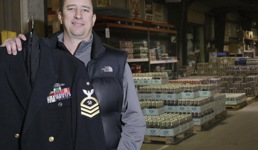 In this Dec. 18, 2015 photo, Mark Mautino, president and owner of Mautino Distributing in Spring Valley, Ill., shows off a U.S. Navy uniform, his other set of work clothes. After his discharge from the U.S.Navy, Mautino decided he missed the camaraderie of military life and decided to part-time it as a Navy reservist. He now is senior chief petty officer, near the top in the non-enlisted chain of command. (Chris Yucus/NewsTribune via AP)
