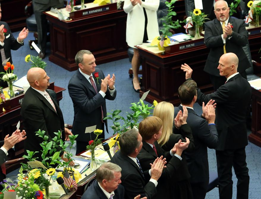 Florida Gov. Rick Scott, right, waves as he is recognized by the house of representatives at the start of the legislative session, Tuesday, Jan.12, 2016, in Tallahassee, Fla. (AP Photo/Steve Cannon)