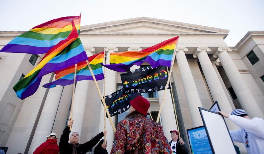 In this file photo, Minoo Vafai, left, holds rainbow flags with others during a rally against Alabama Chief Justice Roy Moore on Tuesday, Jan. 12, 2016, outside the Alabama Supreme Court building in Montgomery, Ala. Supporters of gay marriage rallied Tuesday against Moore and his opposition to same-sex marriage. (Albert Cesare /The Montgomery Advertiser via AP)  NO SALES; MANDATORY CREDIT **FILE**