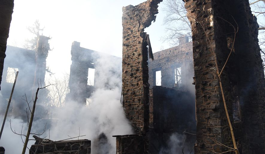 Smoke rises from the smoldering remains of an overnight fire that gutted the Rocky Hill Castle, Tuesday, Jan. 12, 2016, in Chadds Ford Township, Pa. Firefighters had difficulty getting water to the castle, which was built in 1821 on a hill in a wooded area of the township, about 25 miles southwest of Philadelphia. Fire crews were working to determine what caused the fire. (Clem Murray/The Philadelphia Inquirer via AP)  PHIX OUT; TV OUT; MAGS OUT; NEWARK OUT; MANDATORY CREDIT