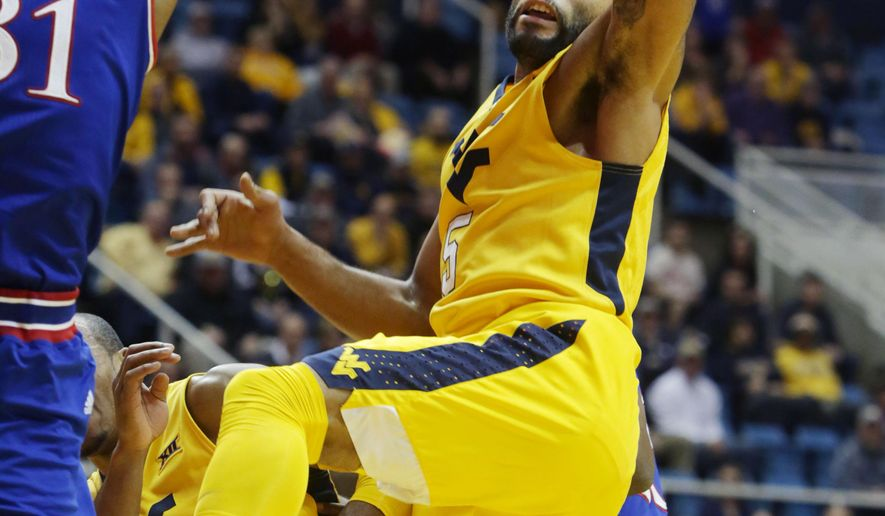 West Virginia guard Jaysean Paige (5) and Kansas forward Jamari Traylor (31) fight for control of a rebound during the first half of an NCAA college basketball game, Tuesday, Jan, 12, 2016, in Morgantown, W.Va. (AP Photo/Raymond Thompson)