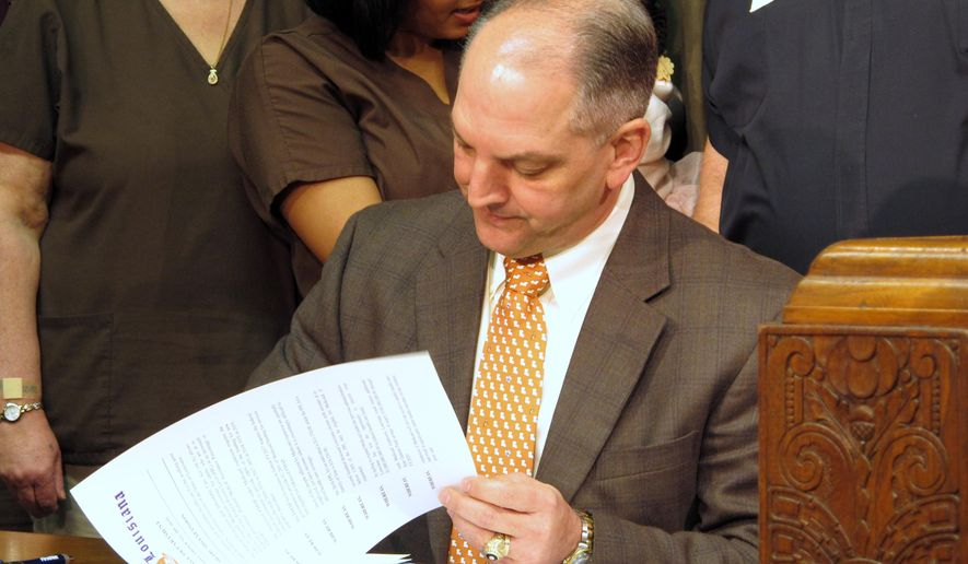 Louisiana Gov. John Bel Edwards signs an  executive order on his first full day in office starting the process for expanding Louisiana's Medicaid program as allowed under the federal health care law, Tuesday, Jan. 12, 2016, in Baton Rouge, La. (AP Photo/Melinda Deslatte)