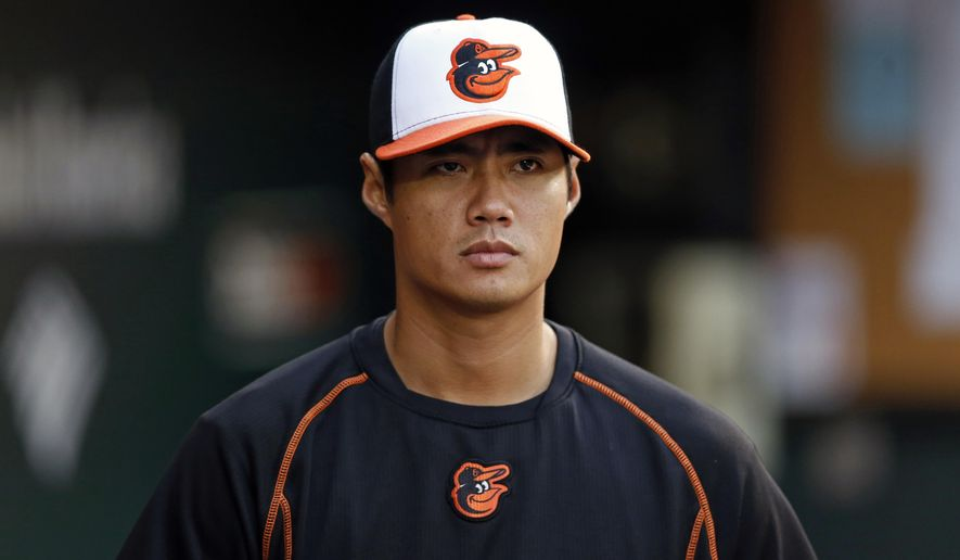 This Sept. 12, 2015 photo shows Baltimore Orioles pitcher Wei-Yin Chen, of Taiwan, walking in the dugout during a baseball game against the Kansas City Royals in Baltimore. The Miami Marlins have fortified their rotation and bench by adding left-hander Wei-Yin Chen and infielder Chris Johnson. Both players agreed to terms, a person close to the negotiations said Tuesday, Jan. 12, 2016. (AP Photo/Patrick Semansky)