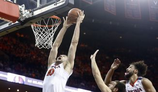 Virginia center Mike Tobey (10) grabs a rebound before dunking during the first half of an NCAA college basketball game against Miami in Charlottesville, Va., on Tuesday, Jan. 12, 2016. (AP Photo/Ryan M. Kelly)