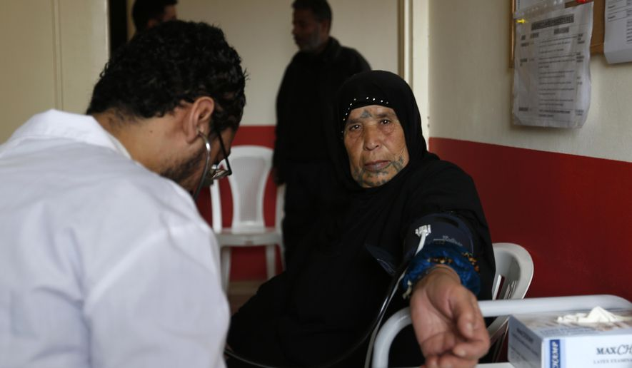 In this Monday, Jan. 4, 2016 photo, a Lebanese medical worker checks a Syrian refugee at a Doctors Without Borders clinic at the Shatila refugee camp in Beirut, Lebanon. In a report published Tuesday, Jan. 12, 2016, the New York-based rights group Human Rights Watch said Lebanese residency laws are putting Syrian refugees in danger. The regulations, adopted a year ago, have forced refugees to either return to Syria, where they are at risk of persecution, torture or death, or to stay in Lebanon illegally, leaving them vulnerable to exploitation and abuse. (AP Photo/Hassan Ammar)