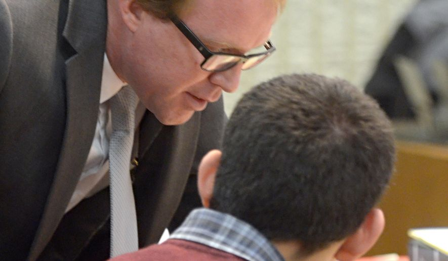 Attorney Stephen Taylor, left, speaks with Nehemiah Griego as a hearing gets underway in Albuquerque, N.M., Monday, Jan. 11, 2016. Griego, who pleaded guilty to killing his parents and three siblings can be rehabilitated and should not be sentenced as an adult, his public defender argued Monday. (Dean Hanson/The Albuquerque Journal via AP) MANDATORY CREDIT