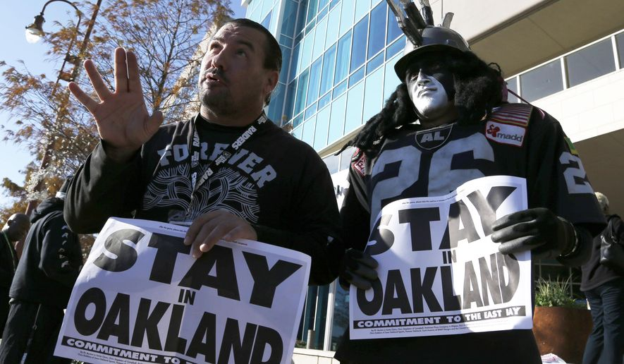 Oakland Raiders fans Griz Jones, left, and Ray Perez make their case for keeping the NFL football team in Oakland outside the hotel where NFL owners are meeting Tuesday, Jan. 12, 2016, in Houston to discuss possible relocation to Los Angeles. (AP Photo/Pat Sullivan)