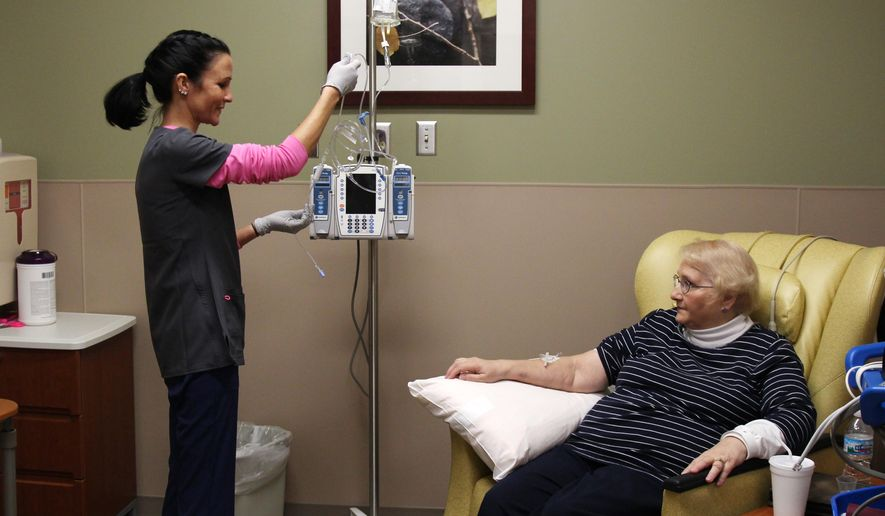 In this Dec. 22, 2015 photo, nurse Nicole Krahn, left, gets rheumatoid arthritis medication ready for semi-retired nurse Lynn Bartos at Froedtert & the Medical College of Wisconsin in Wauwatosa, Wis. The two have switched roles from more than 25 years ago, when Bartos cared for Krahn as a toddler.  (AP Photo/Carrie Antlfinger)