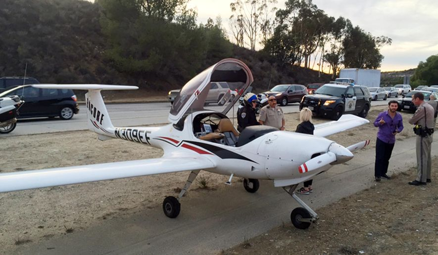 This Monday, Jan. 11, 2016 photo provided by the Ventura County Fire Department shows a two seat airplane after it made an emergency landing on the State Route 23 Freeway in Moorpark, Calif. The California Highway Patrol says vehicles had to swerve to avoid hitting the two-seat aircraft when it touched down after the engine began to sputter. No one was injured.(Ventura County Fire Department via AP)