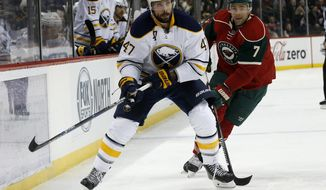 Buffalo Sabres defenseman Zach Bogosian (47) and Minnesota Wild left wing Chris Porter (7) chase the puck during the second period of an NHL hockey game in St. Paul, Minn., Tuesday, Jan. 12, 2016. (AP Photo/Ann Heisenfelt)