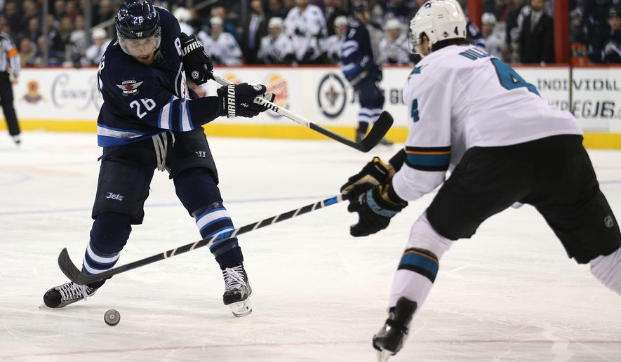 Winnipeg Jets' Blake Wheeler (26) misses as he tries to fire the puck in front of San Jose Sharks' Brenden Dillon (4) during the second period of an NHL hockey game Tuesday, Jan. 12, 2016, in Winnipeg, Manitoba. (Trevor Hagan/The Canadian Press via AP)
