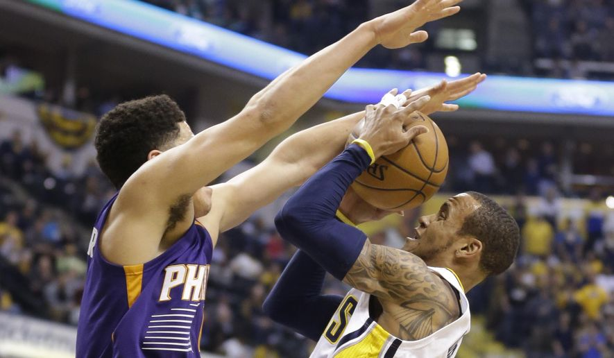 Phoenix Suns guard Devin Booker, left, fouls Indiana Pacers guard Monta Ellis as he shoots during the first half of an NBA basketball game in Indianapolis, Tuesday, Jan. 12, 2016. (AP Photo/Michael Conroy)