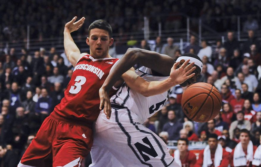 Wisconsin guard Zak Showalter (3) and Northwestern center Dererk Pardon (5) fight for a loose ball during the first half of an NCAA college basketball game, Tuesday,  Jan. 12,  2016. in Evanston, Ill.  (AP Photo/Matt Marton)