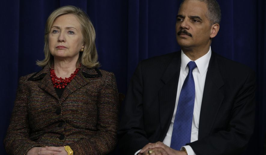 Secretary of State Hillary Rodham Clinton sits on stage with Attorney General Eric Holder as they participate in an International Strategy for Cyberspace event in the South Court Auditorium of the Eisenhower Executive Office Building on May 16, 2011. (Associated Press) **FILE**